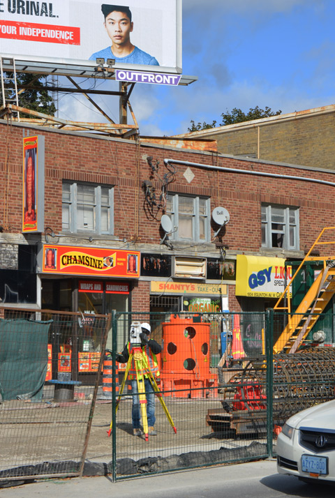 a surveyor at work, behind construction fence and cones and in front of stores, Chamsine, and Shantys take-out, which are two storey brick buildings