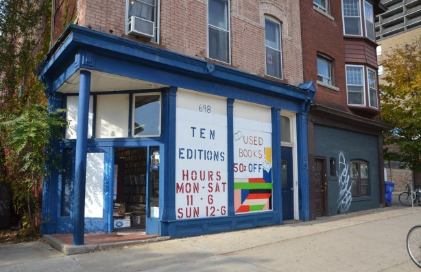 Ten Editions, a used book store on a corner, blue trim, large windows covered with white paper, door is open, stack of boos can be seen inside, old brick building