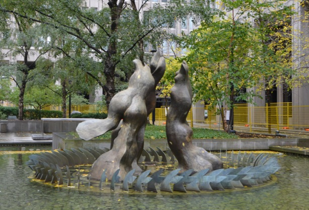a fountain sculpture called Three Graces, in a circle, surrounded by a shallow pool of water
