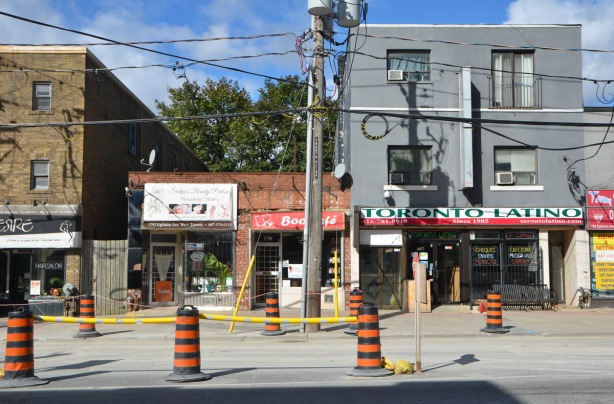 looking across Eglinton Avenue to some stores, construction traffic cones in front,