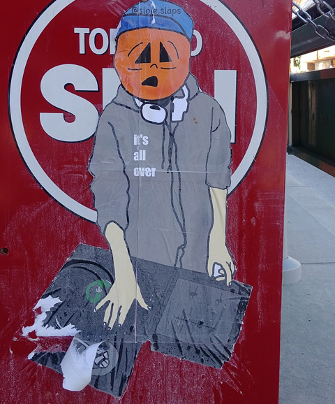 on the side of a red Toronto Sun newspaper box is a large paste up by slole of a person in grey hoodie with a pumpkin head, holding some papers,