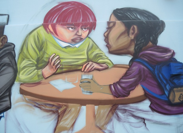 part of a partially completed mural, two girls sitting at a table and talking, one with brown skin and long black hair, one with short red hair, a glass of water in one hand