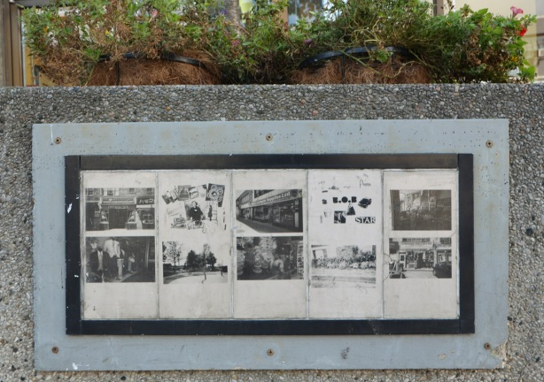 small, old black and white photos reproduced and mounted on the side of a concrete planter outside