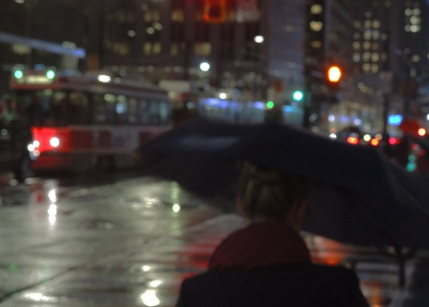 woman with umbrella in the foreground, traffic on a rainy night in the background