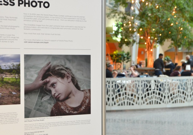 part of a world press photo display at Brookfield Place, with a picture of sick young girl, in the background, people are sitting in a cafe