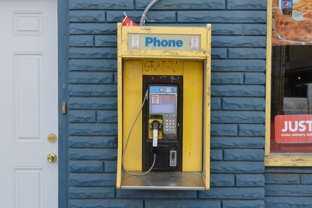 a public phone, small yellow phone booth mounted on a blue brick wall