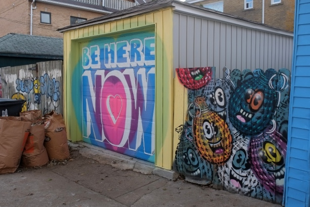 a garage door with the words Be Here Now beside a fence painted with spud bombs, hand grenade shaped characters with eyes and smiling mouths