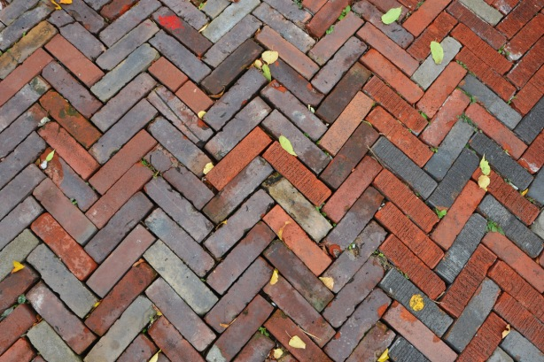 chevron pattern (herring bone pattern) of bricks on a driveway, some autumn leaves on the bricks