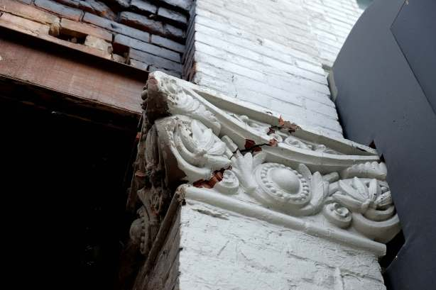 cracked brick wall and decorative carving, on upper storey of an old building