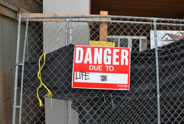 construction site with a danger due to sign that has been altered to say danger due to life