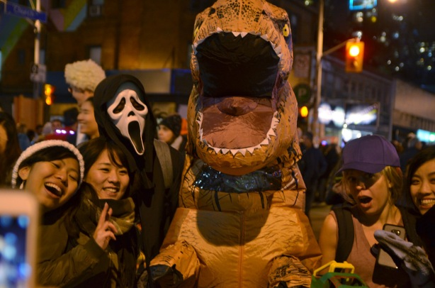 a large inflatable dinosaur costume, a death ghoul costume, and many people standing around them posing for photos at a night time halloween party on Church St., toronto