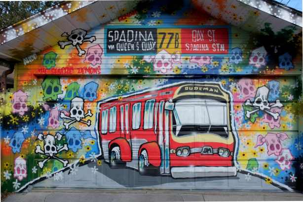 a mural by dudeman, TTX bus, spadina sign, and lots of different coloured skulls