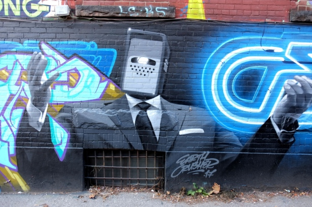 mural in Graffiti Alley by earth crusher - man in black suit, white shirt and black tie, small rectangle machine head and a smart phone in each hand