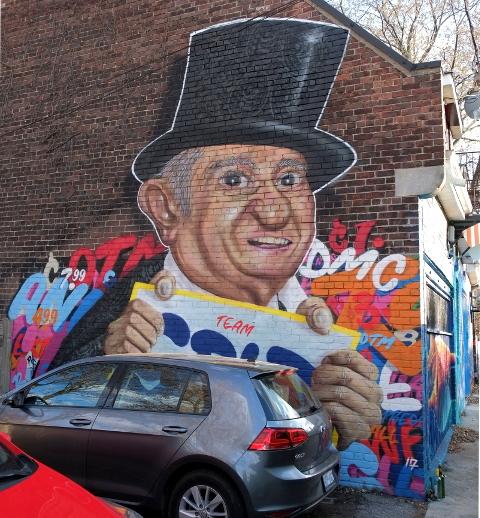 street art portrait of David Mirvish holding iconic Honest Eds signs