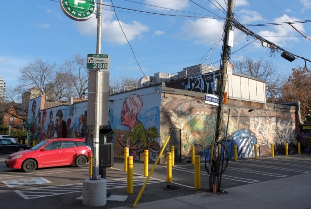 corner where two alleys meet, a green P parking lot and a building with murals on two sides.