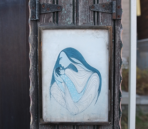 under two hinges, on a post, in front yard of a house, a faded framed print of a mother and her baby