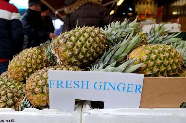 box of pineapples for sale outside a Chinese grocery store, the sign by the box says fresh ginger