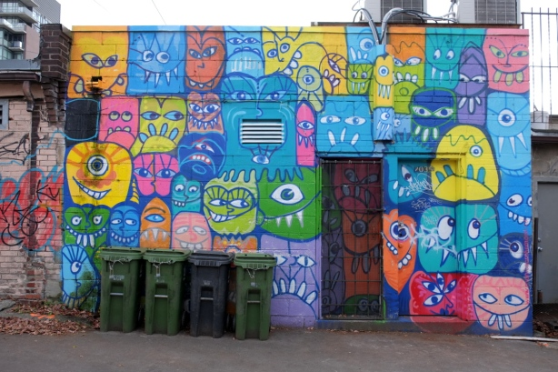 exterior wall in a laneway with mural by monicaonthemoon with many silly stylized faces in bright colours