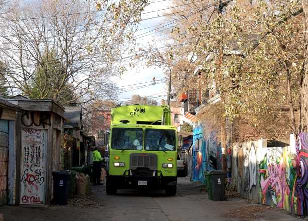 a green GFL garbage truck in a lane as men pick up garbage on garbage day