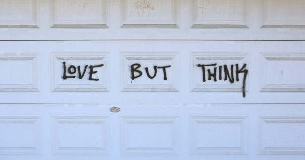 graffiti words on a garage door, love but think