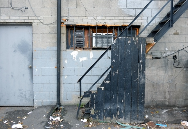 back of a concrete block building in an alley, steel grey door, also small horizontal window with metal grille and air conditioner, metal stairs to upper story painted black, with some black pieces of wood making partial wall beside the stairs.