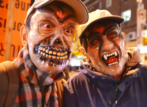 two men in gruesome halloween masks and baseball caps