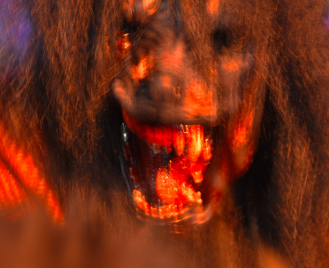 close up of a person in a furry, hairy monstrous mask with bloody fangs