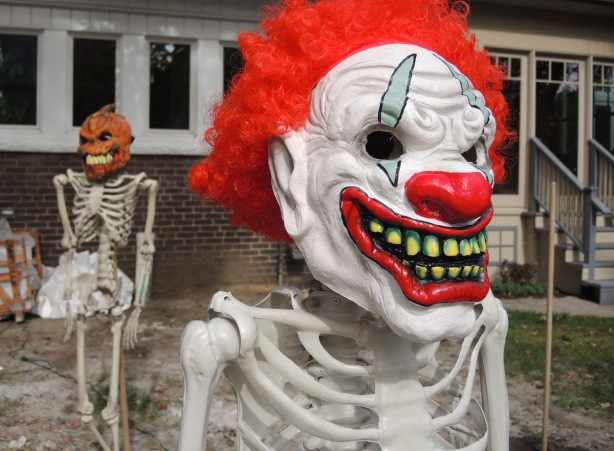 life sized skeleton in a front yard, one with a creepy clown face and one with a pumpkin head