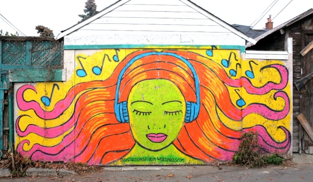 garage door painted with a mural of woman with light skin skin and orange and pink hair with eyes closed and wearing blue headphones. music notes around her head