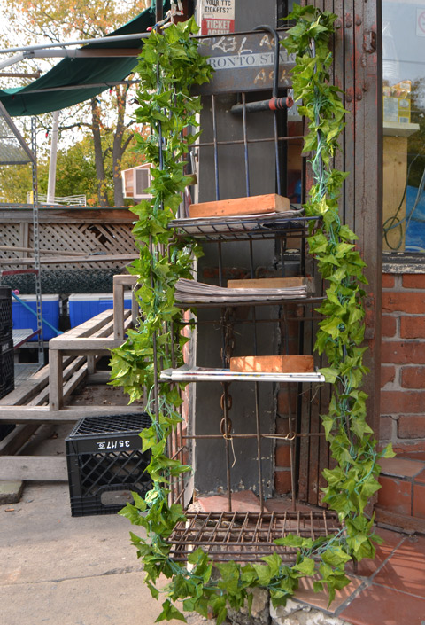 a newspaper rack outside a corner convenience store, the newspapers (there aren't many) are held down with bricks, the rack is decorated with a fake ivy garland