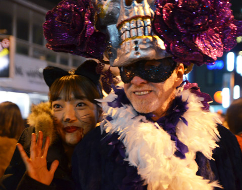 an Asian woman with black cat ears poses with a man in white boa and very large day of the dead head hat