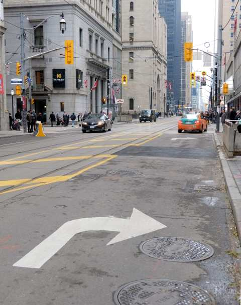 white arrow painted on road directing traffic to turn right
