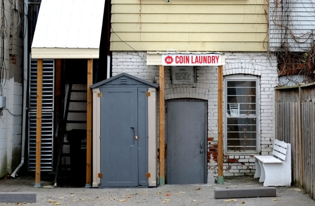 lane entrance to a coin laundry, two grey doors, white bench outside the doors.