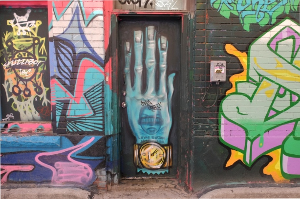 mural in Graffiti Alley - a large blue hand the size of a door, with watch on wrist and words Levar Burton
