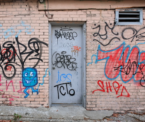 pink brick building with grey metal door, lots of scrawl graffiti on the walls, one litle blue man roughly drawn by the door