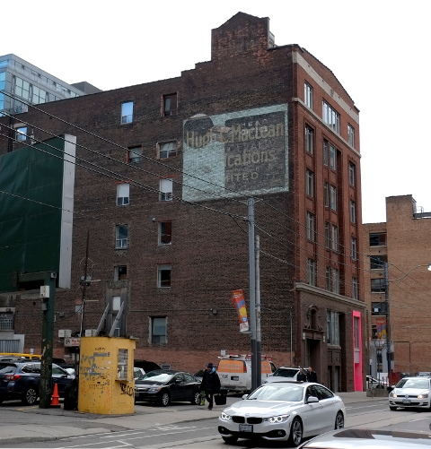 old brick building on Adelaide street, parking lot beside, cars in front, up on top storey (of 6) is an old ghost sign,two in one, one for Hugh C. Macleans publications and another that is too faded to read