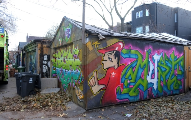 garage with two sides painted in street art, lane, backs of houses, no leaves on tree,