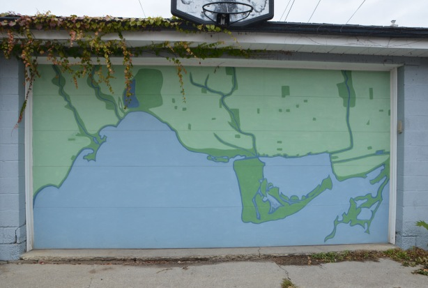 basketball hoop above a garage door that has a large map of Toronto, in blue and green painted on it.
