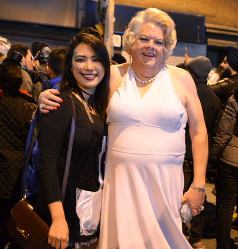a man dressed in drag as Marilyn Munro with blond wig and white dress, posing with an Asian woman