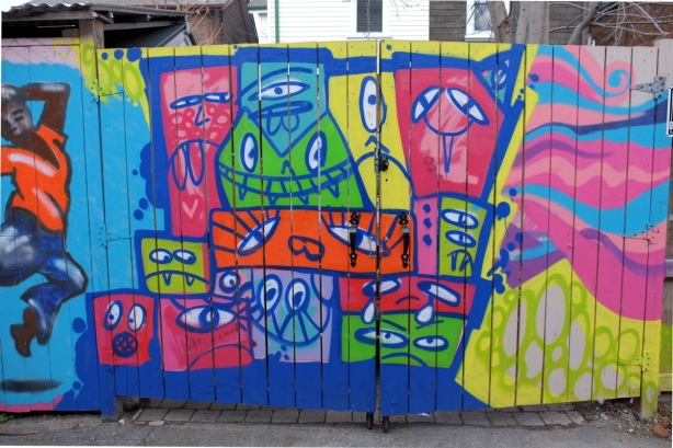 fence in a laneway with mural by monicaonthemoon with many silly stylized faces in bright colours