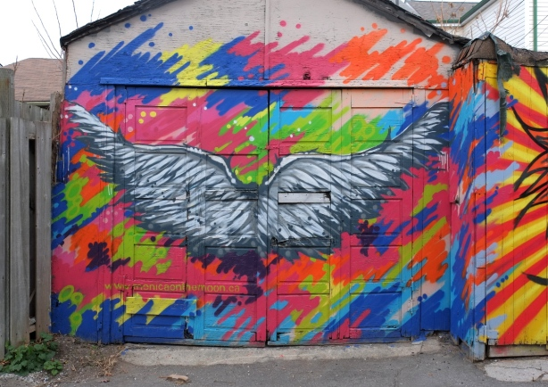 large black and white wings with multicolouredbackground - mural on a garage door in a lane