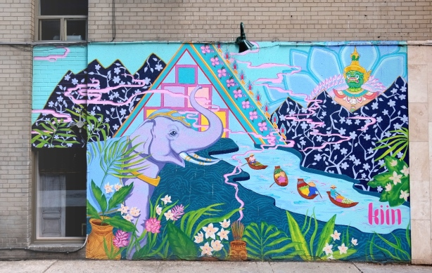 mural on the side of Kiin restaurant, a purple elephant standing beside a river with four boats, flowers growing beside the river.