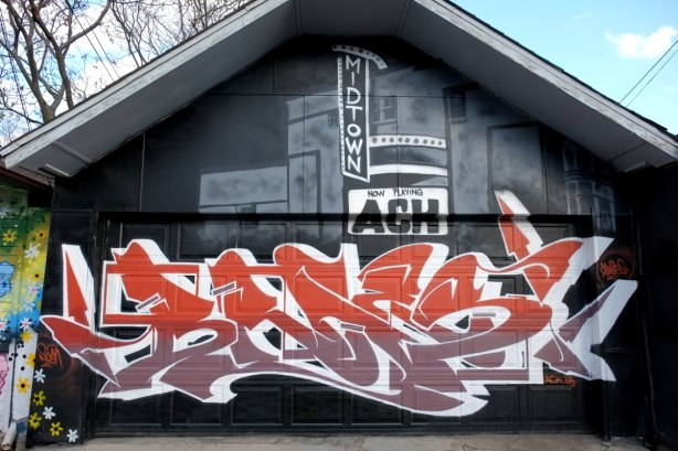 mural on a garage, red and light brown text on the botto, grey tones picture of midtown cinema on the top part