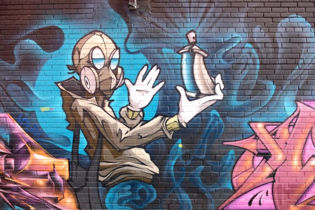 mural in Graffiti Alley - person wearing gas mask and holding a spray paint can in outreached hand