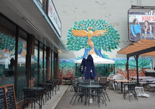 mural on an exterior wall outside Kos restaurant on Bathurst Street, the mural is in the front of the restaurant by the patio, no one sitting outside, blue umbrellas are down.