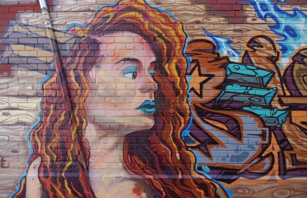 mural of a woman with very long wavy hair, side profile of her head and face, blue lips, blue eyelashes