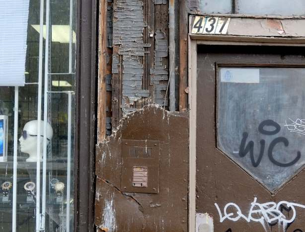 exterior wall, brown paint, number of 437 above the door, cracked wood plywood beside the door, old and broken intercom system that has been painted over, next door window is a store, with mannequin head on a shelf