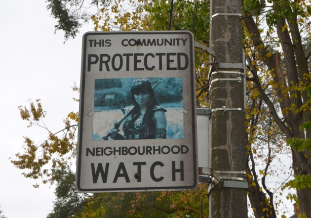 altered neighbourhood watch sign, with a picture in the center,