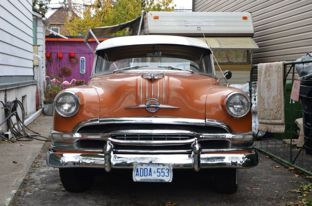 an old orangish brown Chrysler car parked in a driveway, front facing the street,