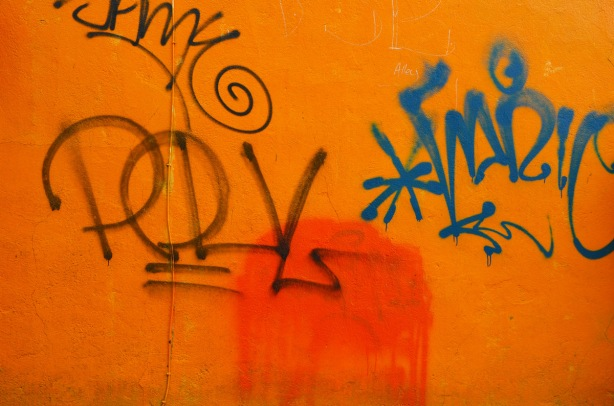 orange stucco wall with graffiti on it.